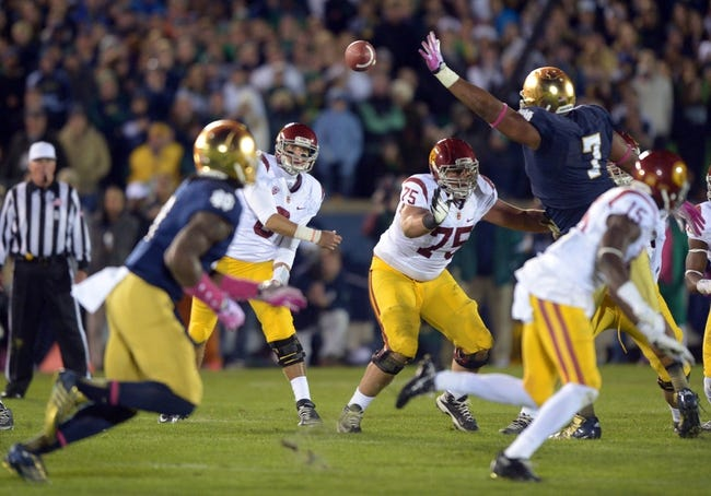 Oct 19, 2013; South Bend, IN, USA; Southern California Trojans quarterback Cody Kessler (6) throws a pass under pressure from Notre Dame Fighting Irish defensive lineman Stephon Tuitt (7) at Notre Dame Stadium. Notre Dame defeated USC 14-10. Mandatory Credit: Kirby Lee-USA TODAY Sports