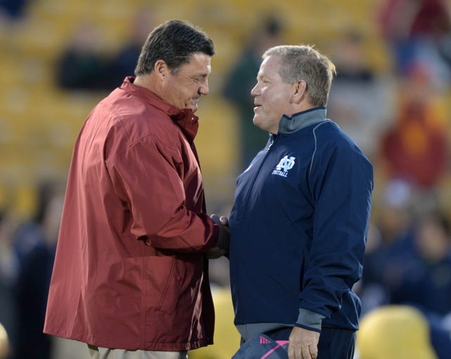 Oct 19, 2013; South Bend, IN, USA; Southern California Trojans coach Ed Orgeron (left) shakes hands with Notre Dame Fighting Irish coach Brian Kelly before the game at Notre Dame Stadium. Mandatory Credit: Kirby Lee-USA TODAY Sports