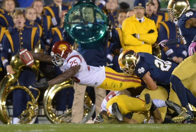 Oct 19, 2013; South Bend, IN, USA; Southern California Trojans tailback Silas Redd (25) is defended by Notre Dame Fighting Irish safety Austin Collinsworth (28) at Notre Dame Stadium. Mandatory Credit: Kirby Lee-USA TODAY Sports