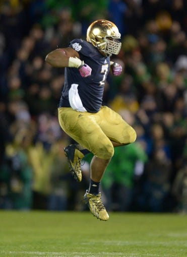 Oct 19, 2013; South Bend, IN, USA; Notre Dame Fighting Irish defensive lineman Stephon Tuitt (7) leaps in celebration in the fourth quarter against the Southern California Trojans at Notre Dame Stadium. Notre Dame defeated USC 14-10. Mandatory Credit: Kirby Lee-USA TODAY Sports