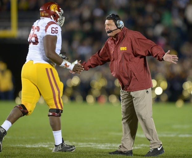 Oct 19, 2013; South Bend, IN, USA; California Trojans coach Ed Orgeron congratulates center Marcus Martin (66) during the game against the Notre Dame Fighting Irish at Notre Dame Stadium. Notre Dame defeated USC 14-10. Mandatory Credit: Kirby Lee-USA TODAY Sports