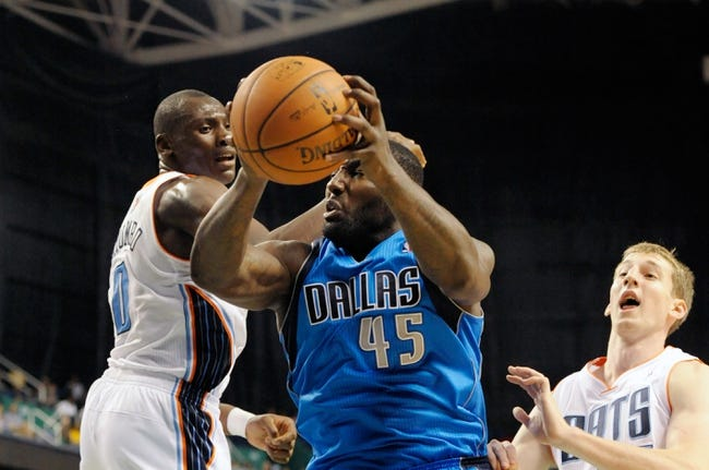 Oct 19, 2013; Greensboro, NC, USA; Dallas Mavericks center DeJuan Blair (45) drives to the basket as he is defended by Charlotte Bobcats forward center Bismack Biyombo (0) during the game at the Greensboro Coliseum. Mavericks win 89-83. Mandatory Credit: Sam Sharpe-USA TODAY Sports