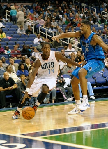 Oct 19, 2013; Greensboro, NC, USA; Charlotte Bobcats forward Michael Kidd-Gilchrist (14) drives past Dallas Mavericks center Fab Melo (14) during the game at the Greensboro Coliseum. Mavericks win 89-83. Mandatory Credit: Sam Sharpe-USA TODAY Sports