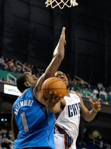Oct 19, 2013; Greensboro, NC, USA; Charlotte Bobcats guard Kemba Walker (15) drives to the basket as he is defended by Dallas Mavericks center Samuel Dalembert (1) during the game at the Greensboro Coliseum. Mavericks win 89-83. Mandatory Credit: Sam Sharpe-USA TODAY Sports