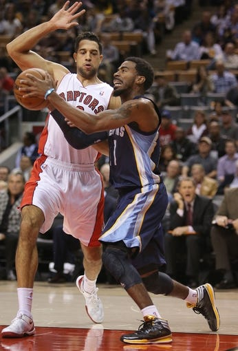 Oct 23, 2013; Toronto, Ontario, CAN; Memphis Grizzlies point guard Mike Conley (11) goes to the basket against Toronto Raptors forward Landry Fields (2) at Air Canada Centre. The Raptors beat the Grizzlies 108-72. Mandatory Credit: Tom Szczerbowski-USA TODAY Sports