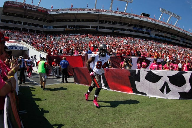 Oct 13, 2013; Tampa, FL, USA; Tampa Bay Buccaneers defensive end Adrian Clayborn (94) runs out of the tunnel before the game against the Philadelphia Eagles at Raymond James Stadium. Mandatory Credit: Kim Klement-USA TODAY Sports