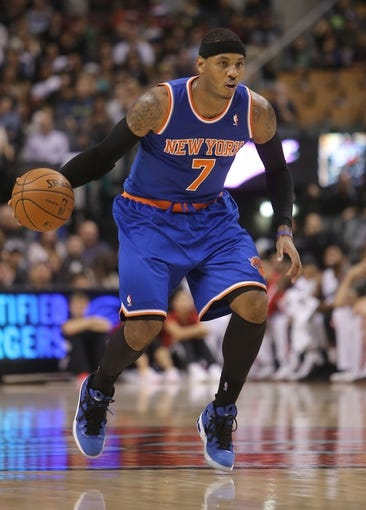 Oct 11, 2013; Toronto, Ontario, CAN; New York Knicks forward Carmelo Anthony (7) with the ball against the Toronto Raptors at Air Canada Centre. The Raptors beat the Knicks 100-91. Mandatory Credit: Tom Szczerbowski-USA TODAY Sports