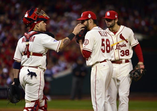 Oct 26, 2013; St. Louis, MO, USA; St. Louis Cardinals starting pitcher Joe Kelly (58) talks with catcher Yadier Molina (4) and shortstop Pete Kozma (38) in the fourth inning against the Boston Red Sox during game three of the MLB baseball World Series at Busch Stadium. Mandatory Credit: Scott Rovak-USA TODAY Sports