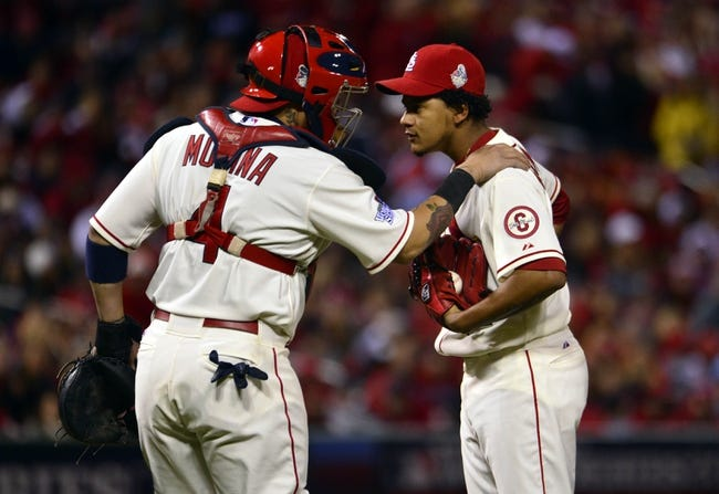 Oct 26, 2013; St. Louis, MO, USA; St. Louis Cardinals relief pitcher Carlos Martinez (right) talks with catcher Yadier Molina (4) in the 8th inning against the Boston Red Sox during game three of the MLB baseball World Series at Busch Stadium. Mandatory Credit: Scott Rovak-USA TODAY Sports