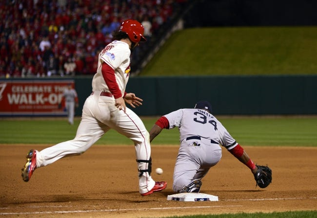 Oct 26, 2013; St. Louis, MO, USA; St. Louis Cardinals second baseman Matt Carpenter (left) beats out the throw to Boston Red Sox first baseman David Ortiz (34) for an infield single in the 7th inningduring game three of the MLB baseball World Series at Busch Stadium. Mandatory Credit: Scott Rovak-USA TODAY Sports