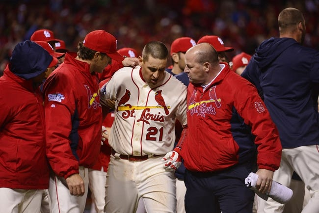 Oct 26, 2013; St. Louis, MO, USA; St. Louis Cardinals pinch hitter Allen Craig (21) is helped off the field by manager Mike Matheny (left) and trainer Greg Houck (right) after Craig scored the winning run in the 9th inning against the Boston Red Sox during game three of the MLB baseball World Series at Busch Stadium. Mandatory Credit: Scott Rovak-USA TODAY Sports