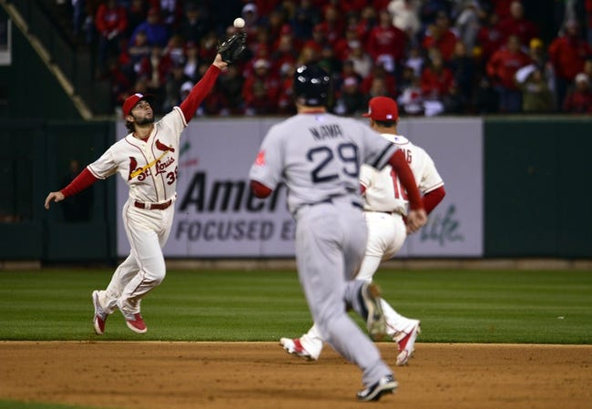 Oct 26, 2013; St. Louis, MO, USA; St. Louis Cardinals shortstop Pete Kozma (38) is unable to field a ball hit for a RBI single by Boston Red Sox shortstop Xander Bogaerts (not pictured) in the 8th inning during game three of the MLB baseball World Series at Busch Stadium. Mandatory Credit: Scott Rovak-USA TODAY Sports
