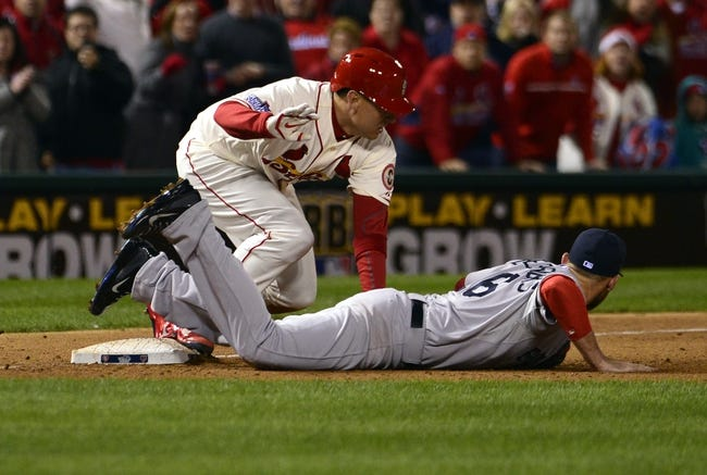 Oct 26, 2013; St. Louis, MO, USA; St. Louis Cardinals pinch hitter Allen Craig (left) slides into third base as the ball gets away from Boston Red Sox third baseman Will Middlebrooks (16) in the 9th inning during game three of the MLB baseball World Series at Busch Stadium. Mandatory Credit: Scott Rovak-USA TODAY Sports