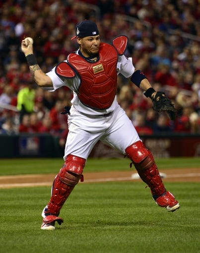 Oct 27, 2013; St. Louis, MO, USA; St. Louis Cardinals catcher Yadier Molina throws to first base against the Boston Red Sox in the first inning during game four of the MLB baseball World Series at Busch Stadium. Mandatory Credit: Scott Rovak-USA TODAY Sports