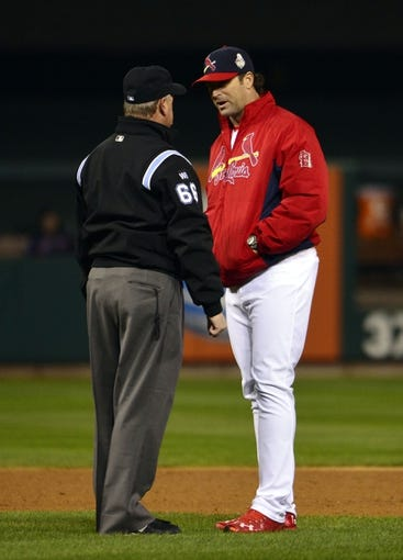 Oct 27, 2013; St. Louis, MO, USA; St. Louis Cardinals manager Mike Matheny (right) argues with umpire Jim Joyce during game four of the MLB baseball World Series against the Boston Red Sox at Busch Stadium. Mandatory Credit: Scott Rovak-USA TODAY Sports