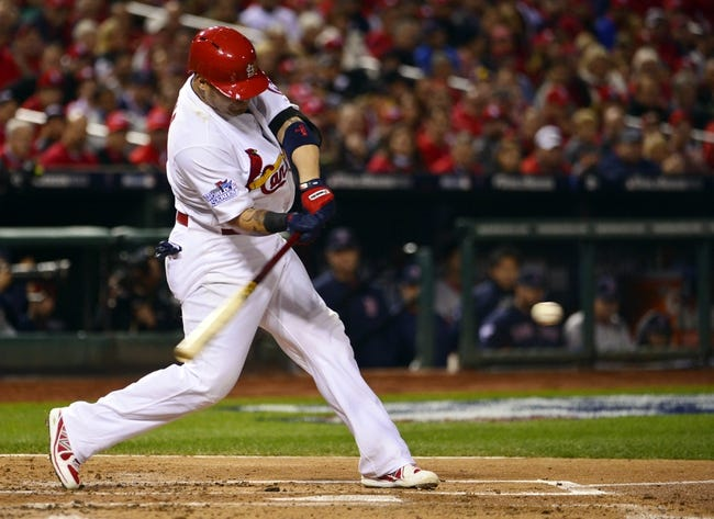 Oct 27, 2013; St. Louis, MO, USA; St. Louis Cardinals catcher Yadier Molina hits a double against the Boston Red Sox in the second inning during game four of the MLB baseball World Series at Busch Stadium. Mandatory Credit: Scott Rovak-USA TODAY Sports