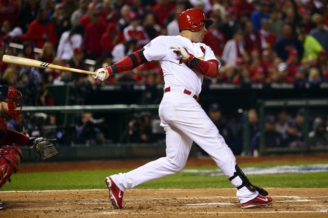 Oct 27, 2013; St. Louis, MO, USA; St. Louis Cardinals right fielder Carlos Beltran hits a RBI single against the Boston Red Sox in the third inning during game four of the MLB baseball World Series at Busch Stadium. Mandatory Credit: Scott Rovak-USA TODAY Sports