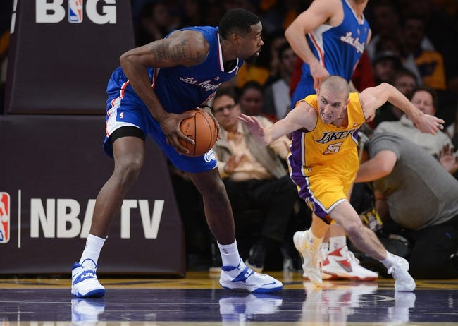 Oct 29, 2013; Los Angeles, CA, USA;  Los Angeles Clippers center DeAndre Jordan (6) keeps the ball from Los Angeles Lakers point guard Steve Blake (5) in the second half of the game at Staples Center. Lakers won 116-103. Mandatory Credit: Jayne Kamin-Oncea-USA TODAY Sports
