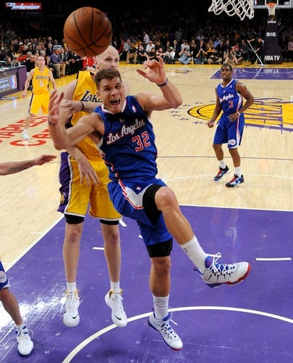 Oct 29, 2013; Los Angeles, CA, USA;   Los Angeles Lakers center Chris Kaman (9) blocks a shot by Los Angeles Clippers power forward Blake Griffin (32) during the game at the Staples Center. Lakers won 116-103. Mandatory Credit: Jayne Kamin-Oncea-USA TODAY Sports