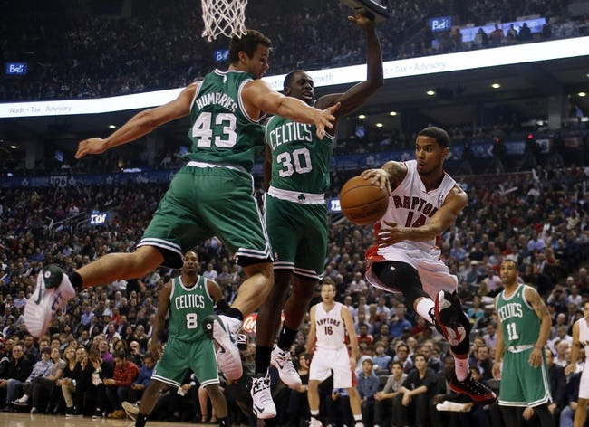 Oct 30, 2013; Toronto, Ontario, CAN; Toronto Raptors guard D.J. Augustin (14) passes the ball as Boston Celtics forward Kris Humphries (43) and forward Brandon Bass (30) defend during the first half at the Air Canada Centre. Mandatory Credit: John E. Sokolowski-USA TODAY Sports