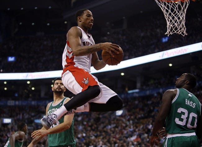Oct 30, 2013; Toronto, Ontario, CAN; Toronto Raptors guard DeMar DeRozan (10) goes up to make a basket as Boston Celtics center Vitor Faverani (38) and Boston Celtics forward Brandon Bass (30) look on at the Air Canada Centre. Toronto defeated Boston 93-87. Mandatory Credit: John E. Sokolowski-USA TODAY Sports
