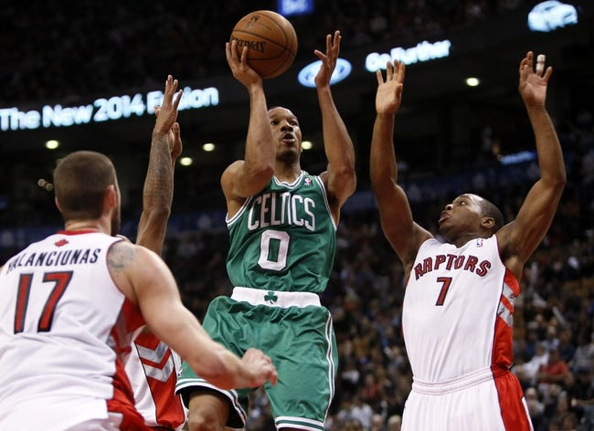 Oct 30, 2013; Toronto, Ontario, CAN; Boston Celtics guard Avery Bradley (0) goes up to make a basket as Toronto Raptors guard Kyle Lowry (7) and  center Jonas Valanciunas (17) defend at the Air Canada Centre. Toronto defeated Boston 93-87. Mandatory Credit: John E. Sokolowski-USA TODAY Sports