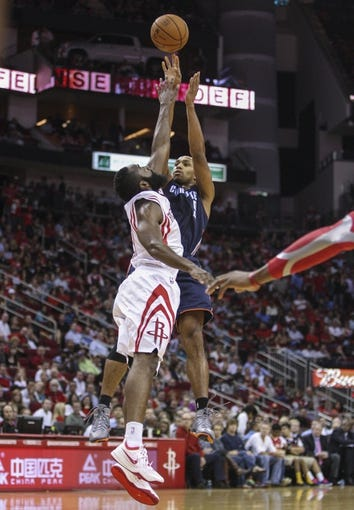 Oct 30, 2013; Houston, TX, USA; Charlotte Bobcats shooting guard Gerald Henderson (9) shoots during the third quarter as Houston Rockets shooting guard James Harden (13) defends at Toyota Center. The Rockets defeated the Bobcats 96-83. Mandatory Credit: Troy Taormina-USA TODAY Sports