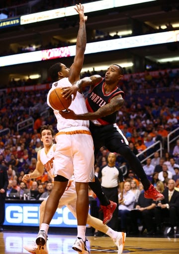 Oct 30, 2013; Phoenix, AZ, USA; Portland Trail Blazers guard Mo Williams (right) passes the ball against Phoenix Suns center Channing Frye in the first half at US Airways Center. Mandatory Credit: Mark J. Rebilas-USA TODAY Sports