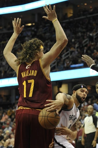 Oct 30, 2013; Cleveland, OH, USA; Brooklyn Nets point guard Deron Williams (8) passes around Cleveland Cavaliers center Anderson Varejao (17) in the third quarter at Quicken Loans Arena. Mandatory Credit: David Richard-USA TODAY Sports