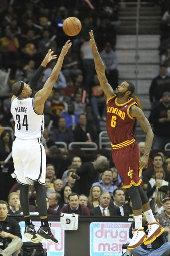 Oct 30, 2013; Cleveland, OH, USA; Brooklyn Nets small forward Paul Pierce (34) makes a basket over Cleveland Cavaliers small forward Earl Clark (6) in the first quarter at Quicken Loans Arena. Mandatory Credit: David Richard-USA TODAY Sports
