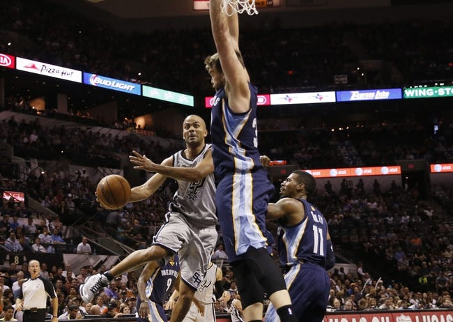 Oct 30, 2013; San Antonio, TX, USA; San Antonio Spurs guard Tony Parker (9) passes the ball under the basket against Memphis Grizzlies center Marc Gasol (right) during the second half at AT&T Center. The Spurs won 101-94. Mandatory Credit: Soobum Im-USA TODAY Sports