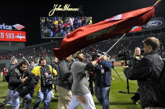 Oct 30, 2013; Boston, MA, USA; Boston Red Sox left fielder Jonny Gomes celebrates by waving a flag after game six of the MLB baseball World Series against the St. Louis Cardinals at Fenway Park. The Red Sox won 6-1 to win the series four games to two. Mandatory Credit: Bob DeChiara-USA TODAY Sports