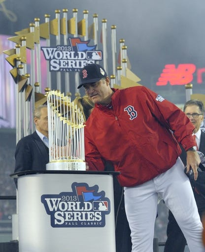 Oct 30, 2013; Boston, MA, USA; Boston Red Sox manager John Farrell looks at the World Series championship trophy after game six of the MLB baseball World Series against the St. Louis Cardinals at Fenway Park. The Red Sox won 6-1 to win the series four games to two. Mandatory Credit: Bob DeChiara-USA TODAY Sports