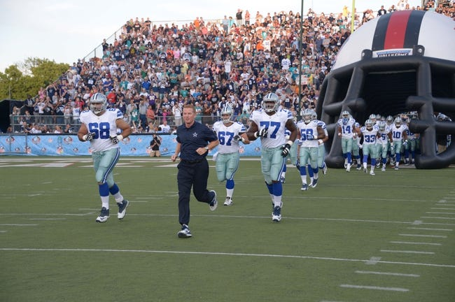Aug 4, 2013; Canton, OH, USA; Dallas Cowboys coach Jason Garrett (center) leads tackles Doug Free (68) and Tyron Smith (77) onto the field before the 2013 Hall of Fame Game against the Miami Dolphins at Fawcett Stadium.  Mandatory Credit: Kirby Lee-USA TODAY Sports