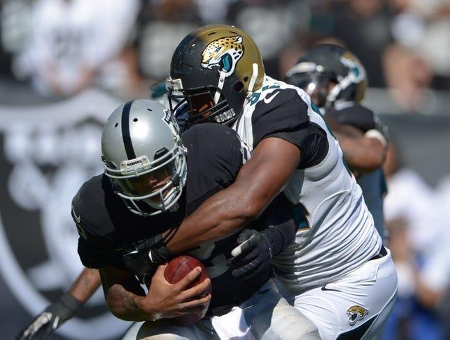 Sep 15, 2013; Oakland, CA, USA; Jacksonville Jaguars defensive lineman Jeremy Mincey (94) sacks Oakland Raiders quarterback Terrelle Pryor (2) at O.co Coliseum. The Raiders defeated the Jaguars 19-9.  Mandatory Credit: Kirby Lee-USA TODAY Sports