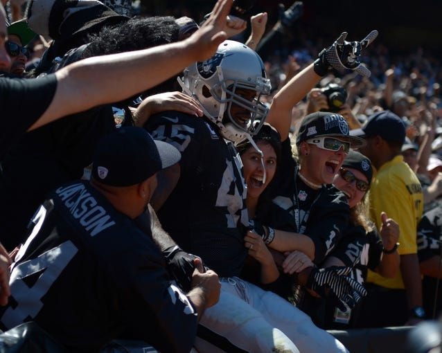 Sep 15, 2013; Oakland, CA, USA; Oakland Raiders fullback Marcel Reece (45) celebrates with fans after scoring on an 11-yard touchdown run in the first quarter against the Jacksonville Jaguars at O.co Coliseum. Mandatory Credit: Kirby Lee-USA TODAY Sports