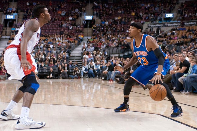 Oct 21, 2013; Toronto, Ontario, CAN; New York Knicks shooting guard Toure' Murry (23) controls the ball against Toronto Raptors point guard Julyan Stone (77) in the second half of a game at the Air Canada Centre.Toronto won the game in triple overtime123-120. Mandatory Credit: Mark Konezny-USA TODAY Sports