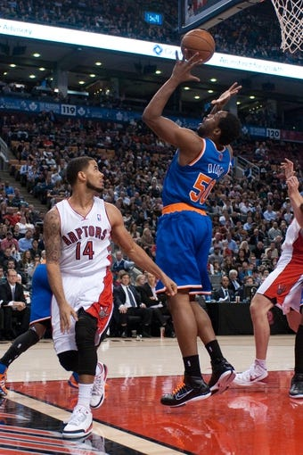 Oct 21, 2013; Toronto, Ontario, CAN; New York Knicks power forward Ike Diogu (50) grabs a rebound with Toronto Raptors point guard D.J. Augustin (14) looking on during the second half of a game at the Air Canada Centre.Toronto won the game in overtime123-120. Mandatory Credit: Mark Konezny-USA TODAY Sports