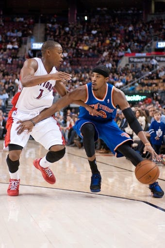 Oct 21, 2013; Toronto, Ontario, CAN; New York Knicks shooting guard Toure' Murry (23) drives the ball past Toronto Raptors point guard Kyle Lowry (7)  in the second half of a game at the Air Canada Centre.Toronto won the game in  overtime123-120. Mandatory Credit: Mark Konezny-USA TODAY Sports