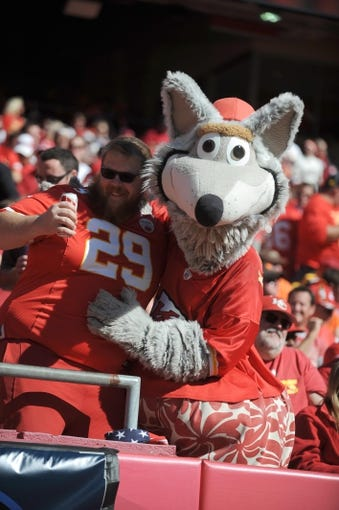 Oct 27, 2013; Kansas City, MO, USA; Kansas City Chiefs mascot KC Wolf poses with a fan during the second half of the game against the Cleveland Browns at Arrowhead Stadium. The Chiefs won 23-17.  Mandatory Credit: Denny Medley-USA TODAY Sports