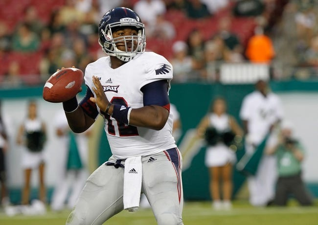 Sep 14, 2013; Tampa, FL, USA; Florida Atlantic Owls quarterback Jaquez Johnson (12) drops back against the South Florida Bulls during the first quarter at Raymond James Stadium. Mandatory Credit: Kim Klement-USA TODAY Sports