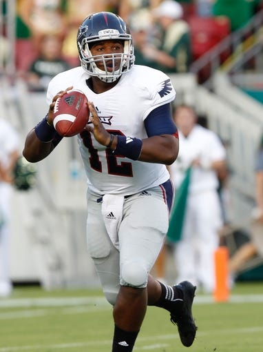 Sep 14, 2013; Tampa, FL, USA; Florida Atlantic Owls quarterback Jaquez Johnson (12) throws the ball during the first quarter against the South Florida Bulls at Raymond James Stadium. Mandatory Credit: Kim Klement-USA TODAY Sports