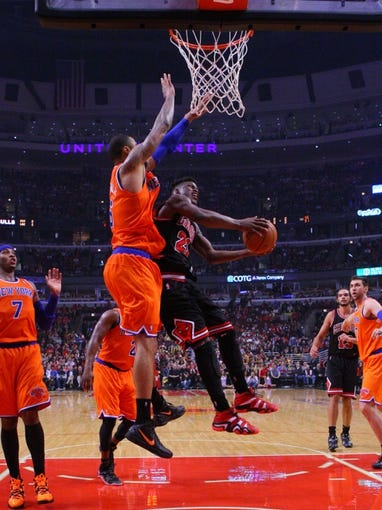Oct 31, 2013; Chicago, IL, USA; Chicago Bulls shooting guard Jimmy Butler (21) shoots past New York Knicks center Tyson Chandler (6) during the second half at the United Center. Chicago won 82-81. Mandatory Credit: Dennis Wierzbicki-USA TODAY Sports