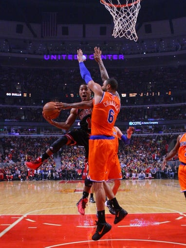 Oct 31, 2013; Chicago, IL, USA; Chicago Bulls point guard Derrick Rose (1) drives past New York Knicks center Tyson Chandler (6) during the second half at the United Center. Chicago won 82-81. Mandatory Credit: Dennis Wierzbicki-USA TODAY Sports