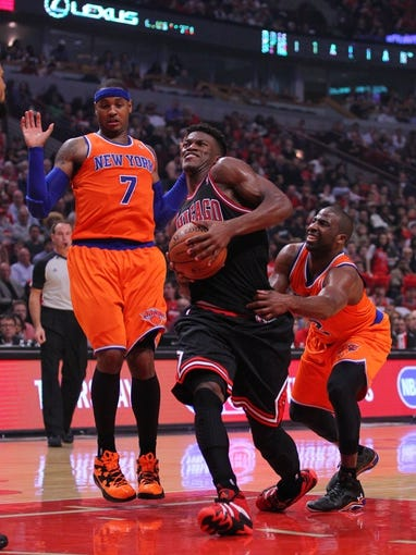 Oct 31, 2013; Chicago, IL, USA; Chicago Bulls shooting guard Jimmy Butler (center) drives between New York Knicks small forward Carmelo Anthony (left) and point guard Raymond Felton (right) during the second half at the United Center. Chicago won 82-81. Mandatory Credit: Dennis Wierzbicki-USA TODAY Sports