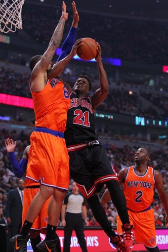 Oct 31, 2013; Chicago, IL, USA; Chicago Bulls shooting guard Jimmy Butler (21) shoots against New York Knicks center Tyson Chandler (6) during the second half at the United Center. Chicago won 82-81. Mandatory Credit: Dennis Wierzbicki-USA TODAY Sports