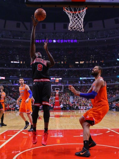 Oct 31, 2013; Chicago, IL, USA; Chicago Bulls small forward Luol Deng (9) scores against New York Knicks center Tyson Chandler (6) during the second half at the United Center. Chicago won 82-81. Mandatory Credit: Dennis Wierzbicki-USA TODAY Sports