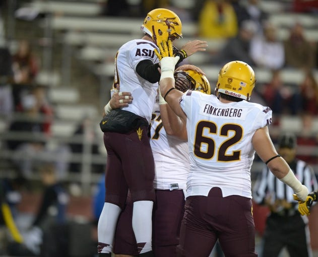 Oct 31, 2013; Pullman, WA, USA; Arizona State Sun Devils quarterback Taylor Kelly (10) celebrates with center Kody Koebensky (67) and left tackle Evan Finkenberg (62) after scoring on a 6-yard touchdown run in the first quarter against the Washington State Cougars at Martin Stadium. Mandatory Credit: Kirby Lee-USA TODAY Sports
