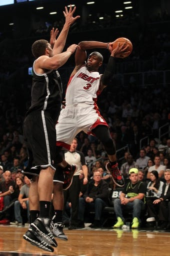 Nov 1, 2013; Brooklyn, NY, USA; Miami Heat shooting guard Dwyane Wade (3) passes from coverage by Brooklyn Nets shooting guard Joe Johnson (7) and Brooklyn Nets center Brook Lopez (11) during the second quarter of a game at Barclays Center. Mandatory Credit: Brad Penner-USA TODAY Sports