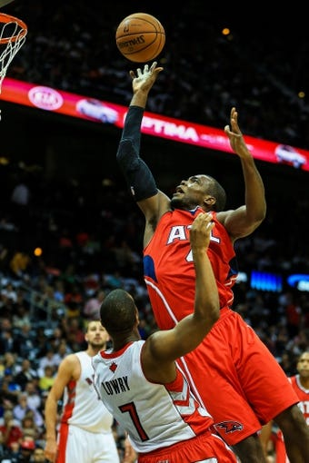 Nov 1, 2013; Atlanta, GA, USA; Atlanta Hawks power forward Paul Millsap (4) shoots a basket over Toronto Raptors point guard Kyle Lowry (7) in the second half at Philips Arena. The Hawks won 102-95. Mandatory Credit: Daniel Shirey-USA TODAY Sports
